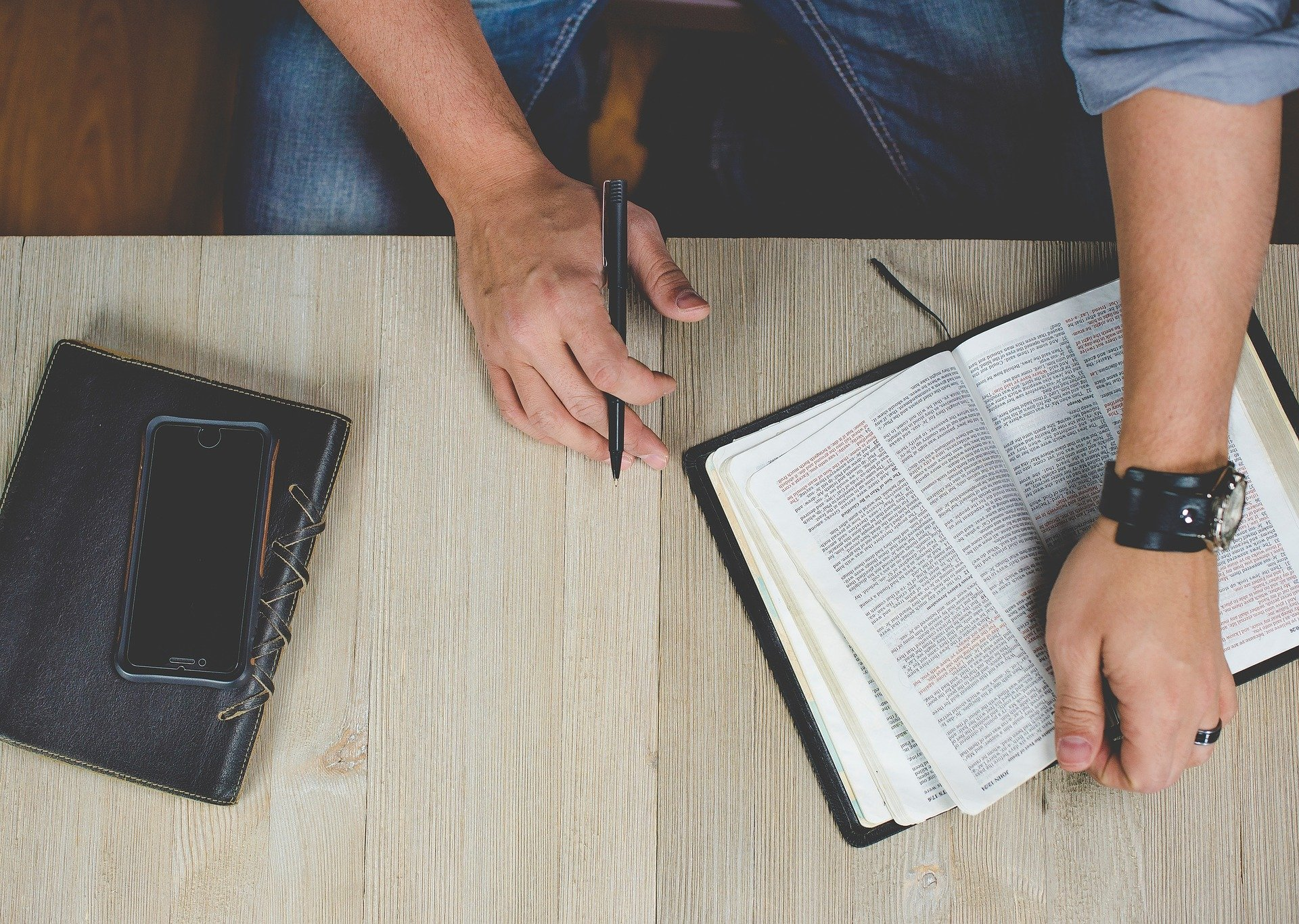 Person holding Bible with phone and journal on table